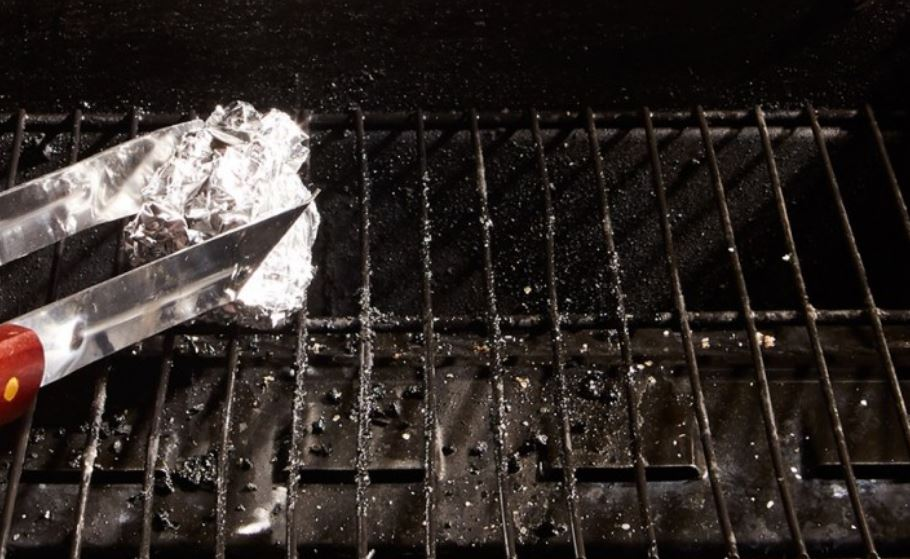 Tongs holding aluminum foil ball for cleaning grill grates