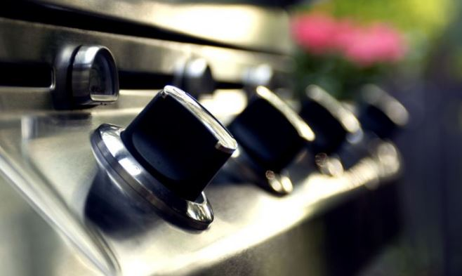 clean knobs on the outside of a stainless steel grill