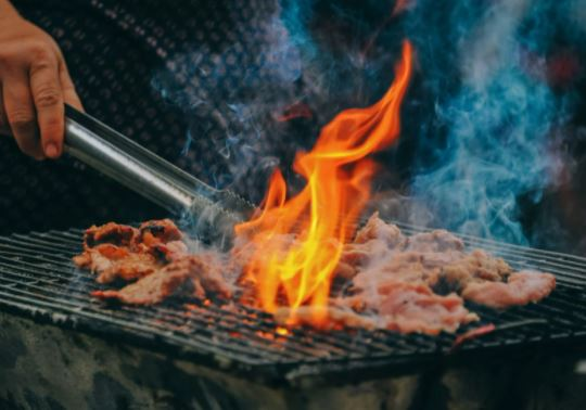 cooking meat over flame on rusty old grill grates