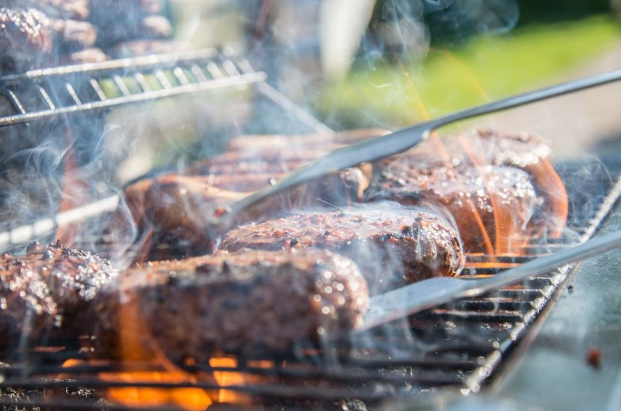greasy barbecue grill with hamburger patties cooking