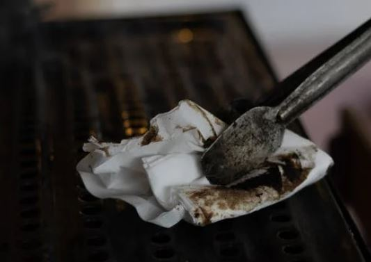 wipe grill with paper tongs held by tongs